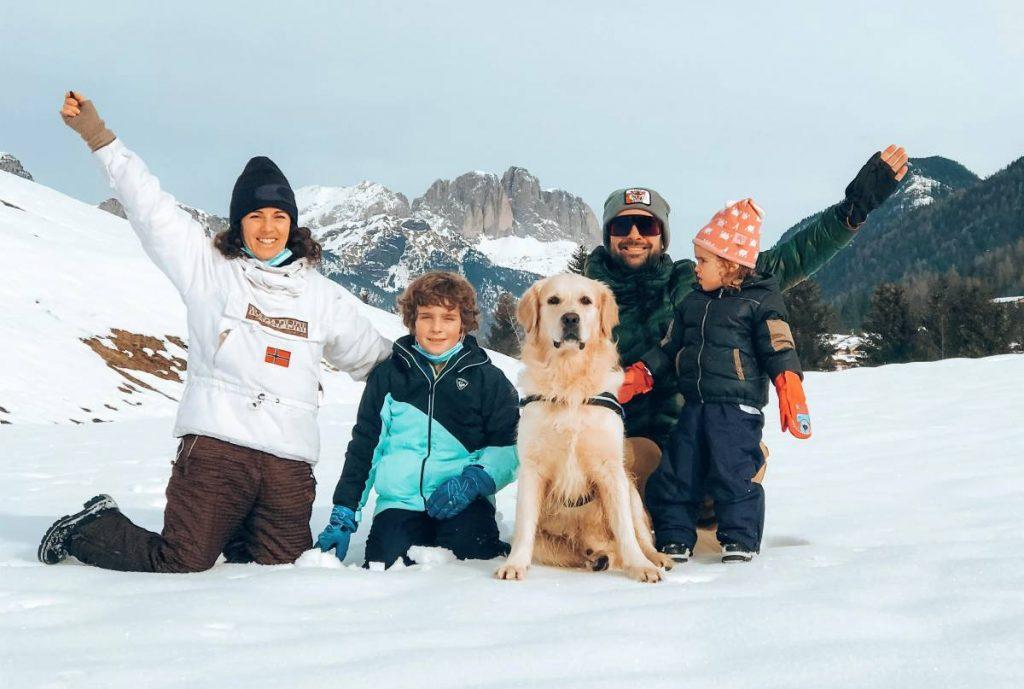 famiglia con cane e bambini sulla neve